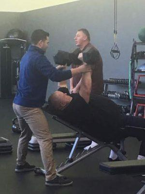 Matthew Lister spots Erin Lundgren as he chest presses 75 pounds in each hand.