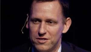 Peter Thiel wearing a suit and tie smiling and looking at the camera: Billionaire Peter Thiel Sells Most Of His Facebook Stock