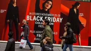 a group of people walking down a street: Black Friday online sales are 3.5 billion