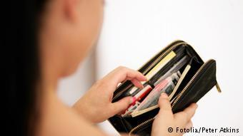 A person reaching into their wallet, Copyright: Fotolia/Peter Atkins