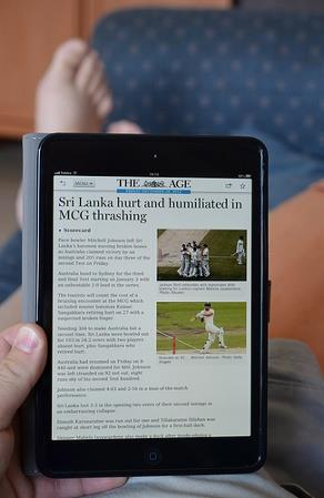 reading newspaper on ipad learning English through the news