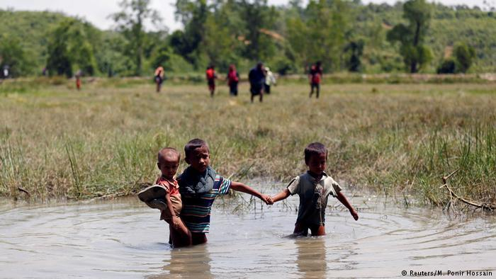 Rohingya children make their way through water