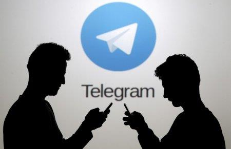FILE PHOTO: Men pose with smartphones in front of a screen showing the Telegram logo in this picture illustration November 18, 2015. REUTERS/Dado Ruvic/File Photo