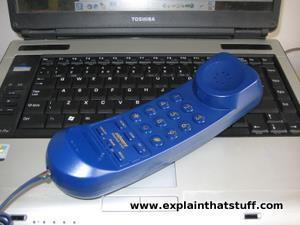 A telephone resting on a laptop.