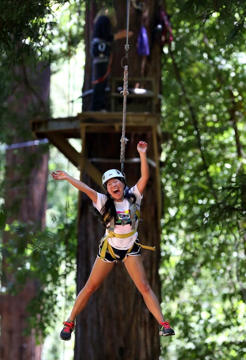 Sarah Chou, an intern with the Careers in Science program, lets out a yell as she careens down a zipline at the ropes course in Eldridge, near Glen Ellen.