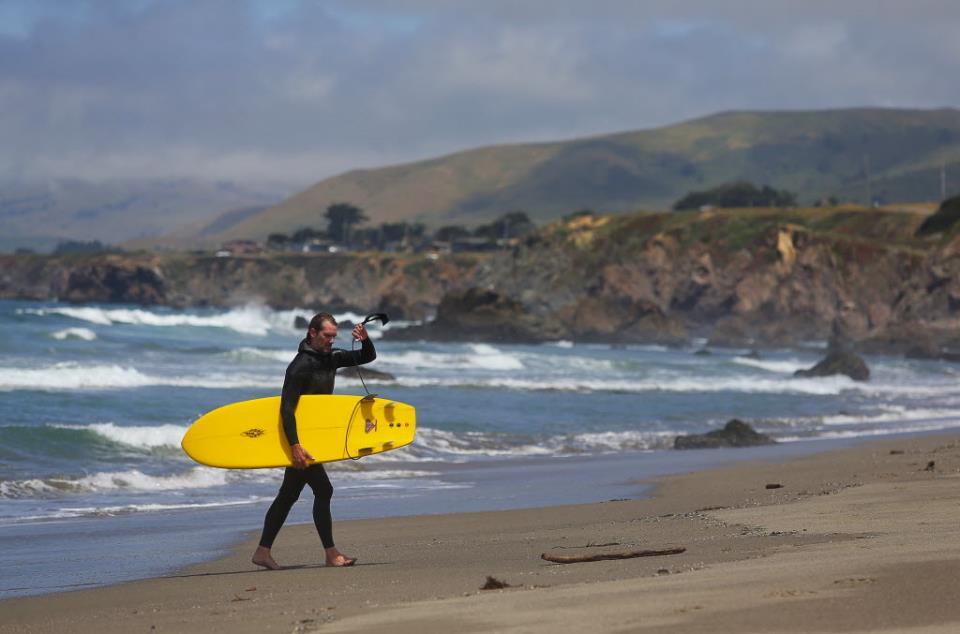 Bill Blaze, of Sebastopol, walks up the beach after surfing at Salmon Creek Beach. (Photo by Christopher Chung)