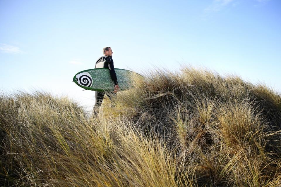 Nate Buck walks through the sand dunes by his home in Salmon Creek to go out for a surf session. (Photo by Conner Jay)