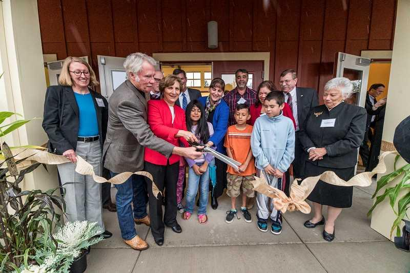 Photo Credit: NEWS-TIMES PHOTO: CHASE ALLGOOD - Oregon Gov. John Kitzhaber and Congresswoman Suzanne Bonamici (second and third from left) help Bienestar Executive Director Karen Shawcross (far right) and several children cut the ribbon opening Juniper Gardens II, a Forest Grove affordable-housing community for farmworkers in Washington County.