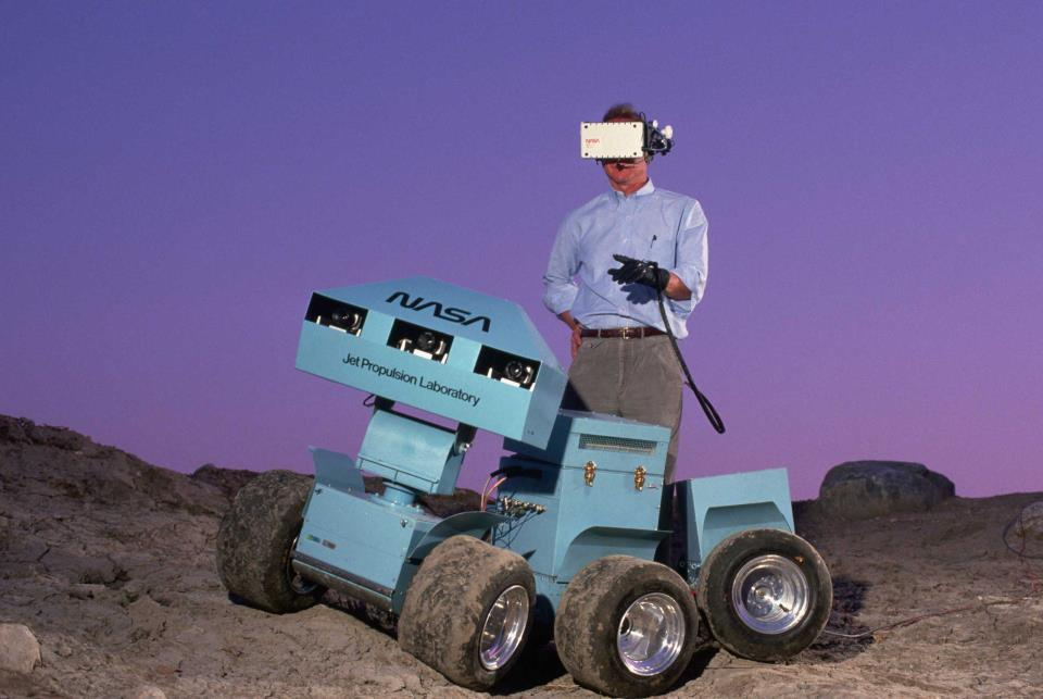 "<strong>1988</strong> Andrew Mishkin wearing a 3-D virtual display helmet that is connected to a six-wheeled roving vehicle. The rover was meant to explore the surface of Mars and send back information.""></div> <div class="