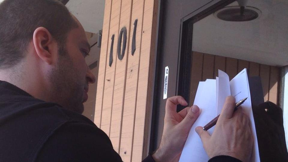 Jan Koum signs the $19 billion Facebook deal paperwork on the door of his old welfare office in Mountain View, Calif. (Photo courtesy of Jan Koum)
